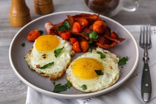Over-medium eggs on a plate with roasted tomatoes and bacon.